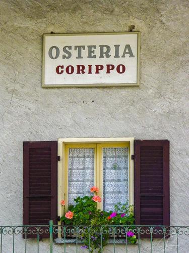 Schild Osteria Corippo über einem Fenster im Valle Verzasca