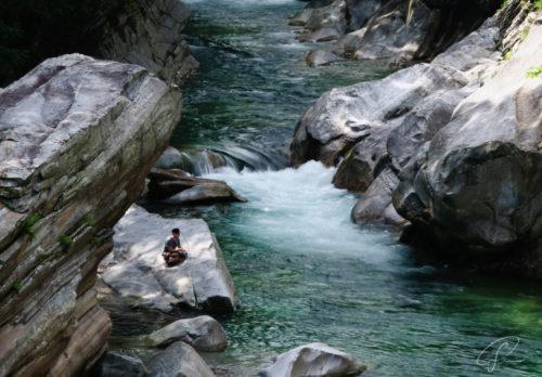 Angler auf den Felsen am Ufer des grünen Verzasca Fluß