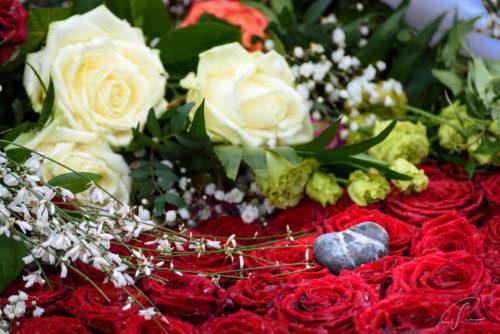 Rote Rosen mit einem Stein auf einem Grab