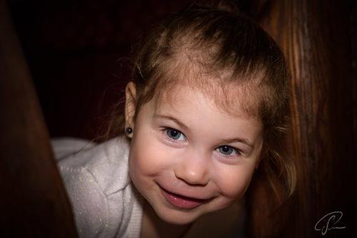 Ein kleines Mädchen schaut zwischen Balken hervor und ruft Hallo