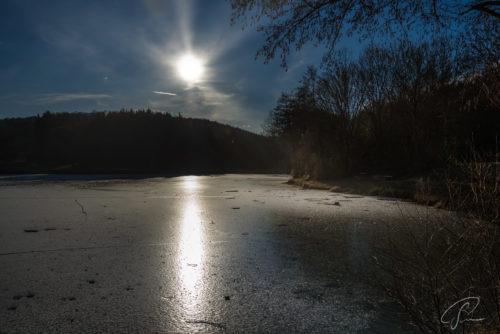 Blick auf den zu Eis gefrorenen Beuerbach See im Gegenlicht