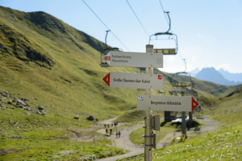 Schilder für Wanderwege und Gondeln der Sesselbahn nahe der Station Höfratsblick am Nebelhorn