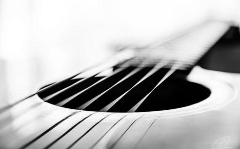 Schwarzweiß Aufnahme eines Schallochs mit den Saiten einer Gitarre als Fineart